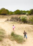 Children running into a dune landscape stock photo
