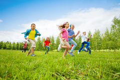 Children are running through green field together royalty free stock image
