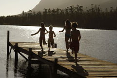 Children Running On Jetty At Lake royalty free stock photo