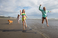 Children running and jumping at the beach. Two kids running and jumping at the beach while mom and the dog chase from behind stock photos