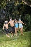 Children running through lawn sprinkler together royalty free stock images