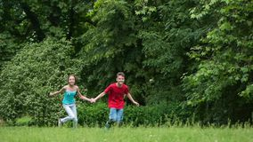 Children running in park. Happy teen boy and girl running through the field towards the camera. Children running and laughing by in grass at summer park stock video