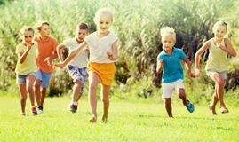 Children running in park. Smiling children in school age running together in park on summer Stock Photography