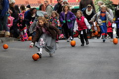 Children running after pumpkins during Pumpkin roll,Saratoga Springs,New York,2013. Several happy,laughing children chasing their own pumpkins down Caroline Royalty Free Stock Images
