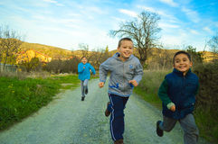 Group of children running a race outdoors Royalty Free Stock Photos