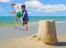 Children running from sand castle Stock Photography