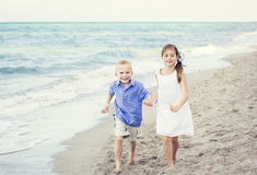 Children running together along the beach Royalty Free Stock Images
