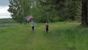 Children running with the U S Flag. Boys running with the US Flag near river in the forest. Children are celebrating 4th july in nature landscape. Summer stock video