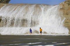 Children running from water crashing over rock Stock Photo
