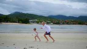 The children runs gleefully along the beach, creating a spray of water stock video