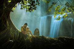 Children in rural sit under a tree on the rocks in a waterfall. stock photography