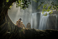 Children in rural sit under a tree on the rocks in a waterfall. stock image