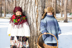 Children in Russian scarf on head with floral print and with  bunch of bagels on background of snow. Royalty Free Stock Photography