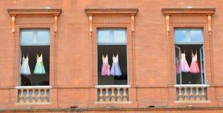 Children& x27; s芭蕾礼服在一栋砖瓦房的窗口里垂悬在城市 免版税库存照片