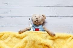 Children& x27; s软的玩具玩具熊在与温度计和药片的床上,采取水银玻璃的温度 在白色 库存图片