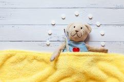 Children& x27; s软的玩具玩具熊在与温度计和药片的床上,采取水银玻璃的温度 在白色 图库摄影