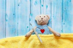 Children& x27; s软的玩具玩具熊在与温度计和药片的床上,采取水银玻璃的温度 在蓝色 免版税图库摄影
