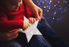 Children`s and adult hands holding Glowing white LED star with garland bokeh background indoor at home. Christmas festive illumination. Happy toddler boy plays stock photo