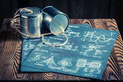 Children`s analog telephone made of cans and string. On old wooden table Stock Photography