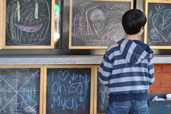 Children's Art in Chalk. Young boy looking at children's artwork on chalk boards Stock Images