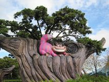 Children`s attraction in Disneyland, Paris. Cheshire cat sitting on a tree. Nice background stock images