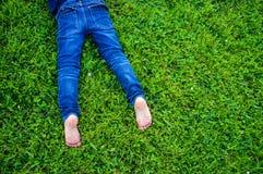 Children's bare feet in blue jeans Stock Photo