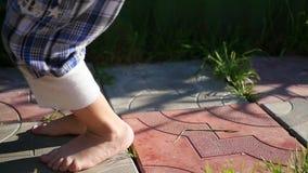 Children`s bare feet run along the path. Fun outdoors. Children`s feet run along the path. Fun outdoors stock video