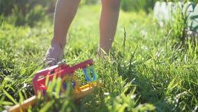 Children`s bare feet running through the grass. Fun outdoors. Children`s feet run along the path. Fun outdoors stock video