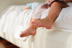 Children's bare feet,  sitting on bed. Baby or Children foot  sitting on the white bed, closeup Royalty Free Stock Image