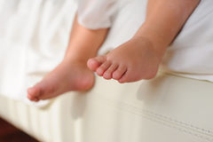 Children's bare feet,  sitting on bed. Baby or Children foot  sitting on the white bed, closeup Royalty Free Stock Photography