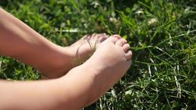 Children`s bare feet stomp across the grass. Fun outdoors stock footage
