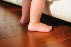 Children's bare feet, beside to bed. Children's bare feet on the wooden floor Royalty Free Stock Photos