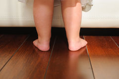 Children's bare feet, beside to bed. Children's bare feet on the wooden floor Royalty Free Stock Photo