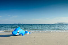 Children's beach toy in Dolphin shape on the beach Stock Photo