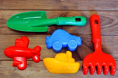 Children`s beach toys on a brown wooden background. Green plastic shovel, red plastic plane, yellow plastic ship, blue plastic car Royalty Free Stock Photos