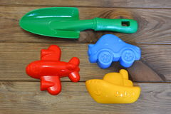 Children`s beach toys on a brown wooden background. Green plastic shovel, red plastic plane, yellow plastic ship, blue plastic car Stock Photos