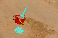 Children`s beach toys - bucket, shovel and pask in the sand on a sunny day. Stock Images