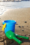 Children's beach toys, bucket and shovel, on sand against the sea Royalty Free Stock Photography