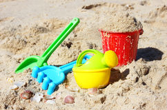 Children's beach toys - bucket, spade and shovel on sand on a sunny day Stock Images