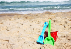 Children's beach toys - bucket, spade and shovel on sand on a sunny day Royalty Free Stock Images