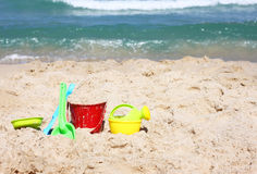 Children's beach toys - bucket, spade and shovel on sand on a sunny day Royalty Free Stock Photos
