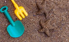 Children`s beach toys - buckets, spade and shovel on sand with space for your texts. Concept of happiness on summer and fun of. Children`s beach toys - buckets stock photos