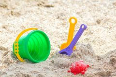 Children`s beach toys - buckets, spade and shovel on sand on a sunny day Stock Photo