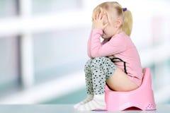 Children& x27; s-Beine, die unten von einem Kammertopf auf einem blauen Hintergrund hängen Lizenzfreie Stockfotos