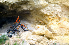 Children`s bicycle on the background of rocks and stones. Orange children`s bicycle with auxiliary wheels. Children`s bicycle is high in the mountains against Royalty Free Stock Photos