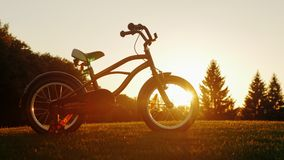Children`s bicycle standing on a green lawn on the background of the setting sun. Concept - children`s dreams, a happy stock video footage