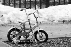 Children`s bike and scooter in the spring Park. Monochrome Royalty Free Stock Photo