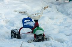 Children's bike in the snow. Thrown a little boy child bicycle snowbound Royalty Free Stock Photography