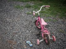 Children`s bikecycle and shoe on stone road. missing children co Royalty Free Stock Image