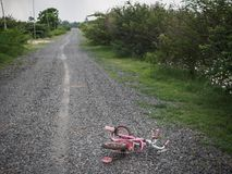 Children`s bikecycle and shoe on stone road. missing children co stock photography